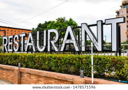 (Restaurant) Letter signs with LED lights. Separate large pieces.  Placed on the sandstone in front of the outdoor building