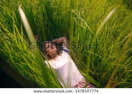 T-shirt design concept - beautiful girl lies in grass in blank white t-shirt in grass #1478597774