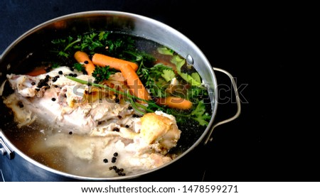 Soup stock in pot viewed from above. Black background and copy space