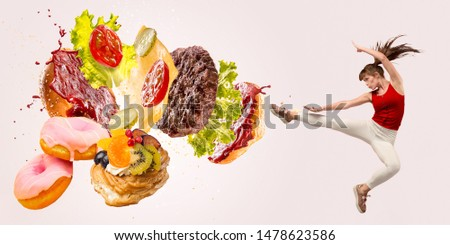 Fight the fast food. Burger's crashing by the boxer isolated on white background. Combination of buns, vegetables, sauce and cutlet is broken by sportswoman. Healthy eating, diet and sport concept. #1478623586