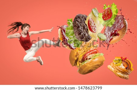 Fast food. Young caucasian woman fights with unhealthy nutrition. Kicks burger or sandwich in jump on red background. Copyspace for your ad. Creative collage about food, weight loss, healthy eating. #1478623799