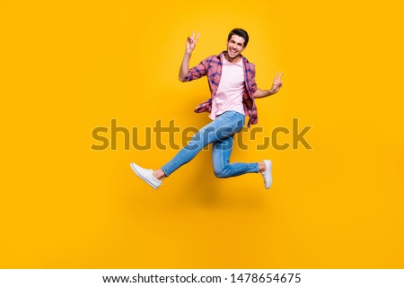 Photo of man running on air showing you v-sign in order to say hi while isolated with yellow background #1478654675