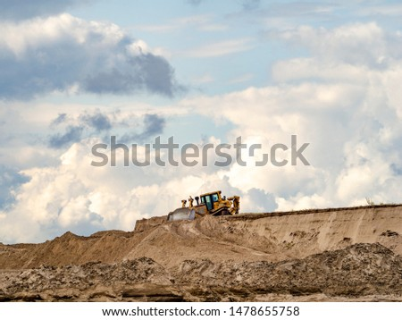A bulldozer is developing a sand pit for construction on a background of sky with clouds #1478655758