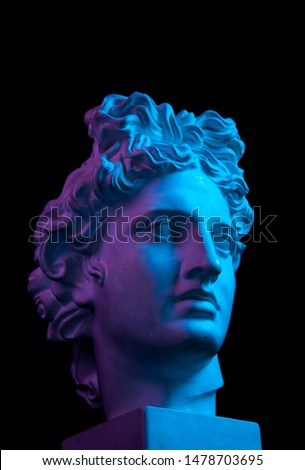 Gypsum copy of ancient statue Apollo head isolated on black background. Plaster sculpture man face. Royalty-Free Stock Photo #1478703695