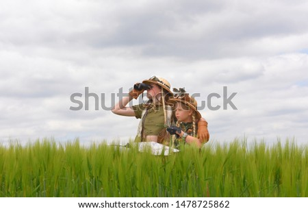 Two young girls dress up as explorers.They pose in  a prairie grassland countryside dressed with jungle  hats and khaki safari clothes. #1478725862