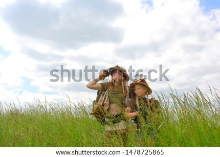 Two young girls dress up as explorers.They pose in  a prairie grassland countryside dressed with jungle  hats and khaki safari clothes. #1478725865