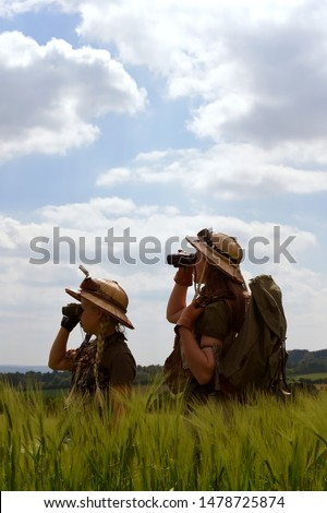 Two young girls dress up as explorers.They pose in  a prairie grassland countryside dressed with jungle  hats and khaki safari clothes. #1478725874