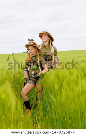Two young girls dress up as explorers.They pose in  a prairie grassland countryside dressed with jungle  hats and khaki safari clothes. #1478725877