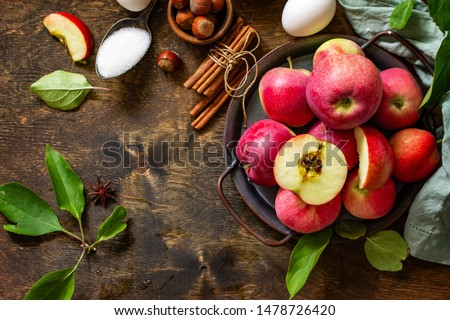 Apple baking seasonal concept. Ingredients for apple pie (red apple, flour, eggs, anise, sugar, hazelnut and cinnamon) on a rustic wooden table. Top view flat lay. Free space for your text. #1478726420