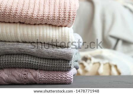 A stack of warm sweaters in the interior of the room.  #1478771948