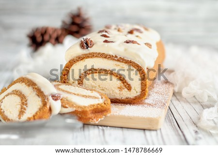 Beautiful fresh baked pumpkin spice roll cake with powdered sugar, pecans, cream cheese filling and icing. Extreme selective focus with blurred background.