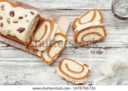 Beautiful fresh baked pumpkin spice roll cake with powdered sugar, pecans, cream cheese filling and icing over white rustic table background. Top view. Overhead.