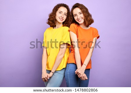 charming shy twins posing to the camera, isolated blue background. studio shot. studio shot, family #1478802806