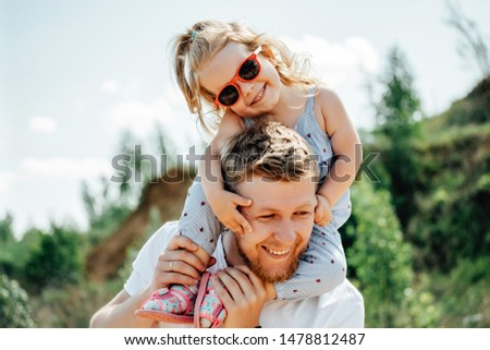Little girl sitting on father's shoulders and laughing. Summer day, happy family and summer lifestyle concept. #1478812487