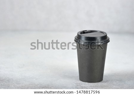Paper cup with coffee. The paper cup is black, the lid is black plastic. The concept of fast food and coffee to go. Light background. Free space for text.  #1478817596