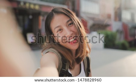 Cheerful beautiful young Asian backpacker blogger woman using smartphone taking selfie while traveling at Chinatown in Beijing, China. Lifestyle backpack tourist travel holiday concept. Point of view. #1478828960