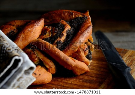 Bread with poppy seeds, a knife on a folk napkin on a rustic table. Holiday Macovei. #1478871011