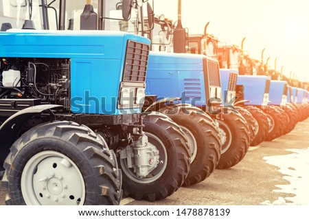 Many different tractors standing in row at agricultural fair for sale outdoors.Equipment for agriculture.Heavy industrial machines presented to an agricultural exhibition #1478878139