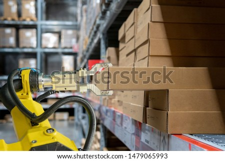 yellow robotic arm carry cardboard box in warehouse Royalty-Free Stock Photo #1479065993