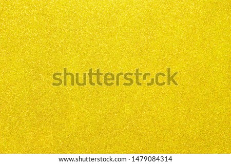 Yellow glitter. Abstract shiny background. Texture of lemon designer paper for decoration and design of Christmas, New Year or other holiday pictures. Beautiful packaging material.