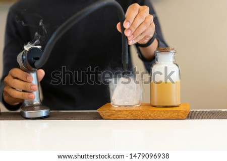 barista smoking and making ice coffee for customer  #1479096938