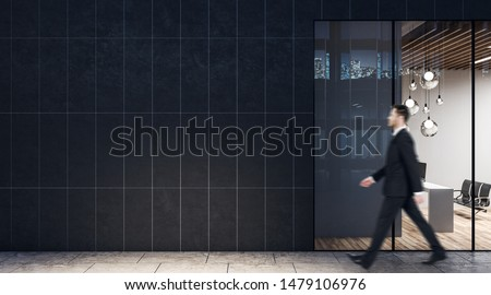 Businessman walking past dark wall business center with modern light conference room with wooden floor and black chairs. #1479106976