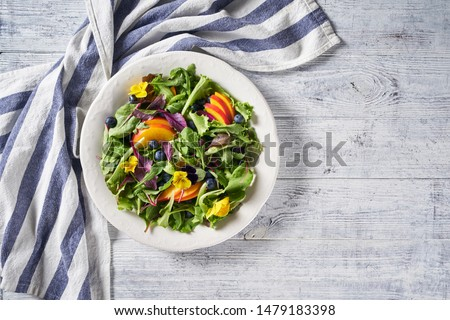 Salad of fresh green leaves, fruits, and berries of arugula, baby spinach, purple chard, watercress, lettuce with edible flowers, blueberries, and peaches on a white plate, top view, copy space #1479183398