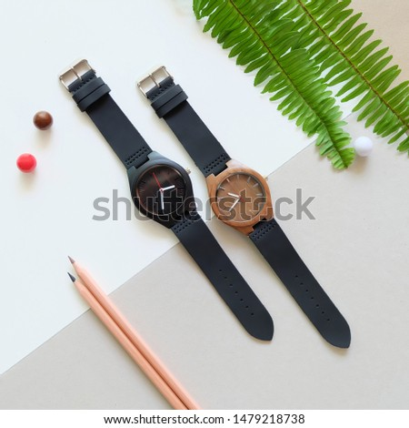 Top view of 2 black wooden watches on white and brown color background. Green leafs,pencil and leather band watch on soft color background. Royalty-Free Stock Photo #1479218738