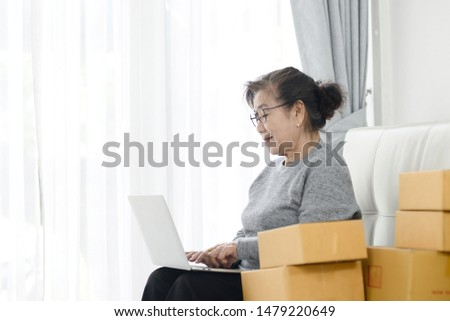 Asian senior woman using laptop while selling online with packaging, work at home concept. #1479220649