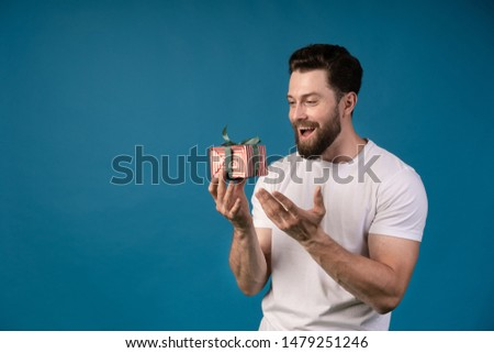 Image of a handsome young excited man posing isolated over blue wall background holding present gift box. Portrait of a handsome man.