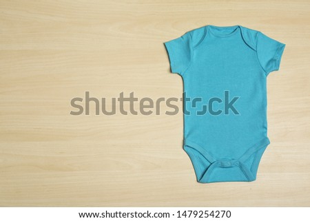 Cute baby onesie on wooden background, top view. Space for text #1479254270