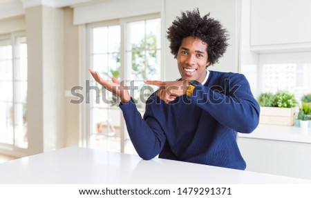Young african american man wearing casual sweater sitting at home amazed and smiling to the camera while presenting with hand and pointing with finger. #1479291371