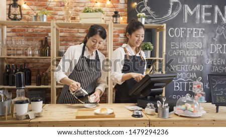 Happy female coffeehouse staff using digital tablet at cafe counter. two smiling waitress chatting gossip while working in modern coffee store. woman barista pour hot latte in cup preparing order. #1479294236