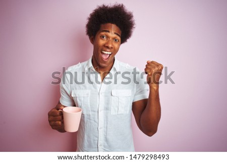 Young african american man drinking a cup of coffee standing over isolated pink background screaming proud and celebrating victory and success very excited, cheering emotion #1479298493