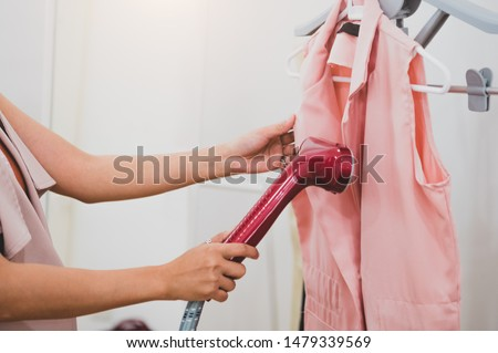 Woman using steaming iron to ironing fashion shirt in laundry room. Girl doing stream vapor iron for press clothes in hand. Launder concentrate work and delivery to customer. Part time job occupation #1479339569