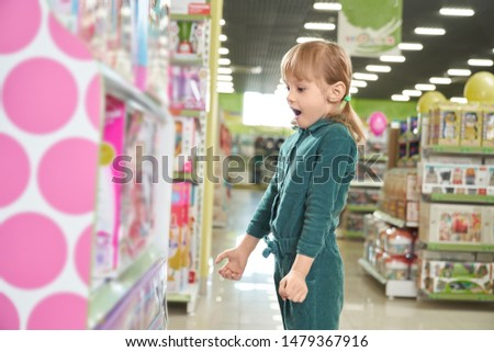 Surprised girl with open mouth standing in big shop with toys and looking at cool playthings. Funny little child choosing and buying games in supermarket. Concept of dream and childhood. #1479367916