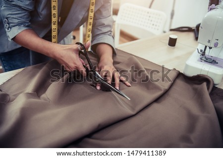Dressmaker cutting dress fabric on sketch line with sewing machine. Fashion designer tailor or sewer in workshop studio designing new collection clothes. Business owner shop and entrepreneur concept #1479411389