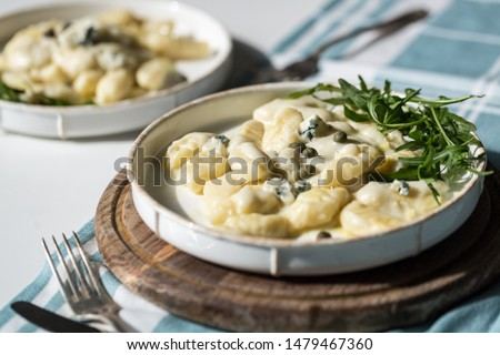 Homemade gnocchi with creamy gorgonzola sauce, capers and arugula in white plate on wooden board. #1479467360