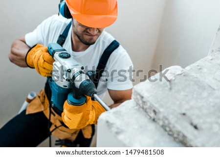 overhead view of handyman in helmet and yellow gloves using hammer drill  #1479481508