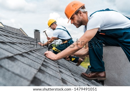selective focus of handsome handyman repairing roof with coworker  #1479491051
