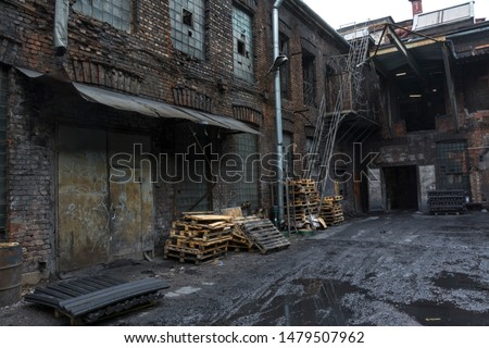 The dirty courtyard of the old factory. Old brick walls and gates #1479507962