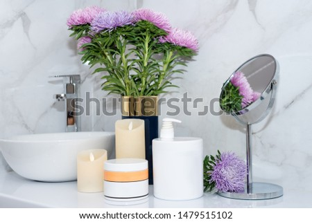 Set of natural cosmetics in beauty salon. Jars of body or hair care product on table with flowers. Space for text #1479515102