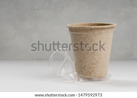 disposable paper cup standing on a crumpled plastic cup #1479592973
