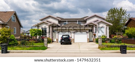 Residential duplex townhouse with black car parked on concret driveway #1479632351