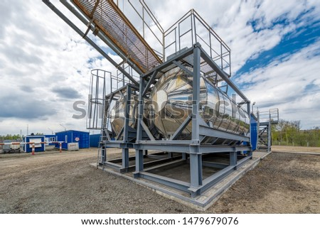 Street tanks for storing various liquids. Tanks are connected by many different pipelines. These pipelines are located deep above the ground. #1479679076