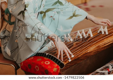 A woman wearing kimono is playing a traditional Japanese musical instrument  Koto, a Japanese harp. #1479822506
