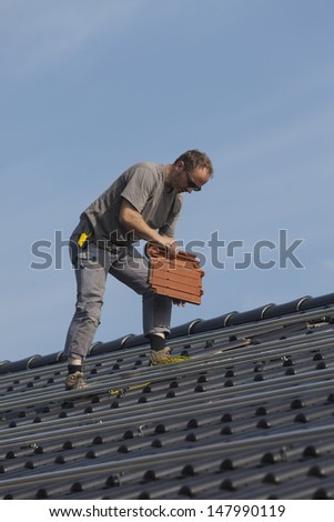 worker preparing the roof to install alternative energy photovoltaic solar panels. #147990119