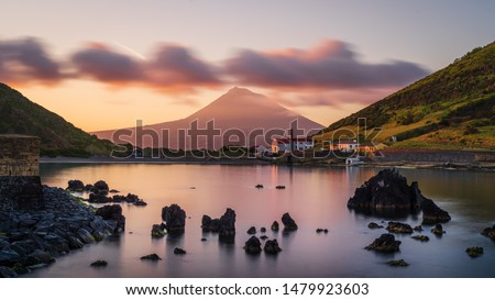 Colourful Sunrise in Horta, Faial Island: long Exposure of the Porto Pim Beach, the Whaling Station and the Pico Volcano Mountain in the background, Azores Islands, Portugal. Royalty-Free Stock Photo #1479923603