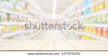Empty wood table top with abstract supermarket grocery store aisle blurred defocused background with bokeh light for product display #1479936242