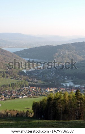 A view of a forest, the Soła river, the Międzybrodzkie lake and a city in the valley in the mountain range of Little Beskids in southern Poland #1479936587